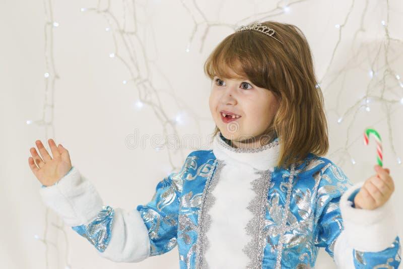 A menina desdentado feliz no terno azul da donzela da neve acenou seu bastão do caramelo na surpresa fotos de stock royalty free