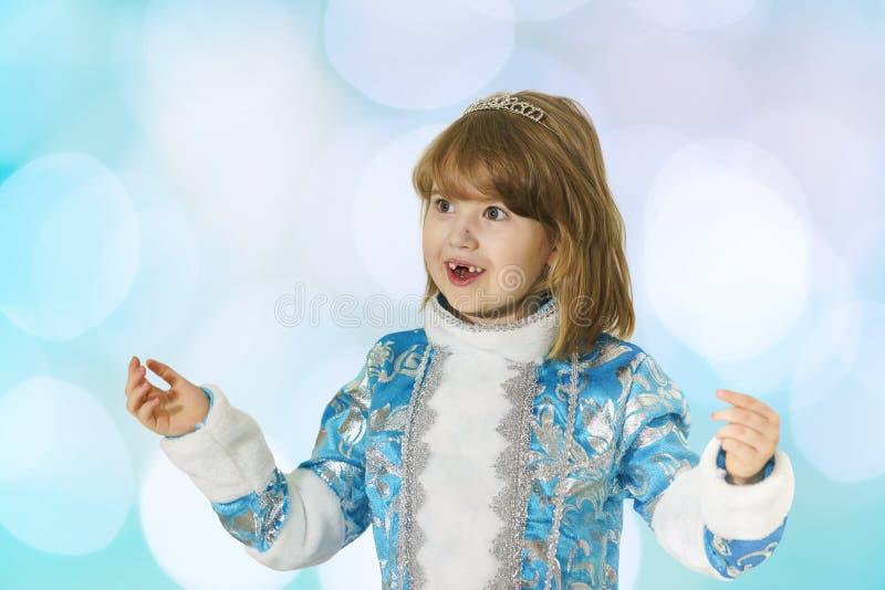 A menina desdentado feliz no terno azul da donzela da neve acenou suas mãos na surpresa fotografia de stock