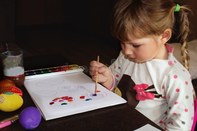 A menina desenha O desenho das crianças para a Páscoa, ovos de pintura imagem de stock