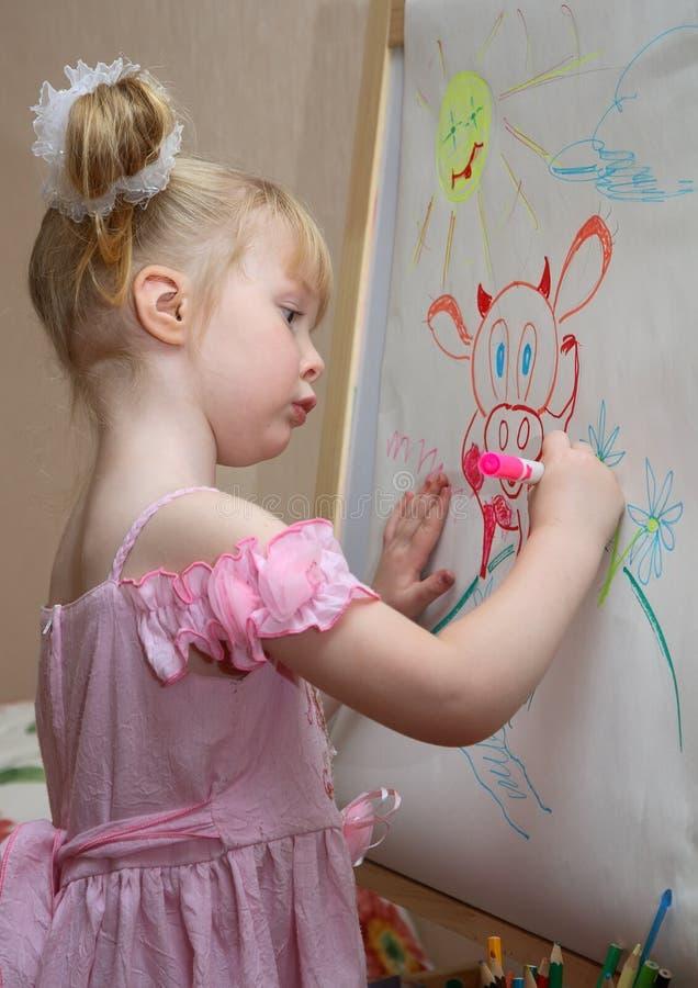 A menina desenha uma vaca fotografia de stock royalty free