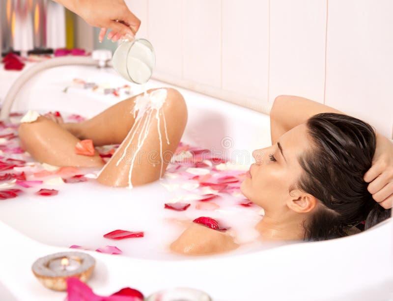 A menina despida atrativa aprecia um banho com leite e as pétalas cor-de-rosa imagem de stock royalty free