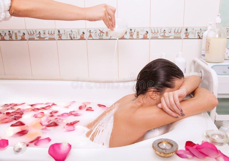 A menina despida atrativa aprecia um banho com leite e as pétalas cor-de-rosa fotografia de stock royalty free
