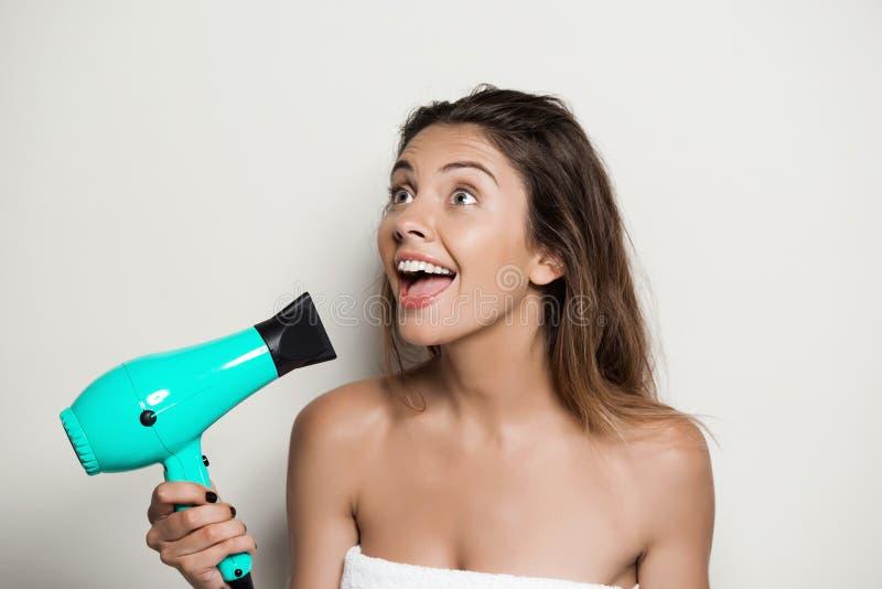 Menina despida bonita nova na toalha que canta com hairdryer fotografia de stock