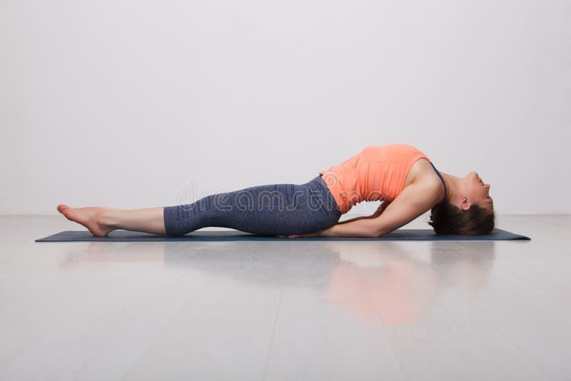 A menina desportiva bonita do iogue do ajuste pratica a ioga fotos de stock