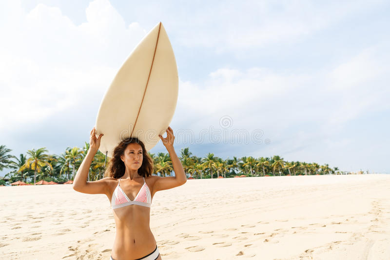Menina desportiva bonita do surfista na praia imagem de stock