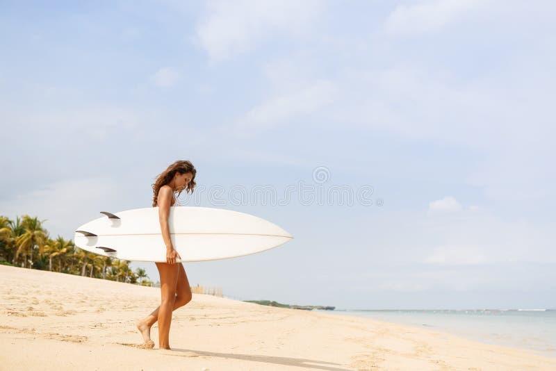 Menina desportiva bonita do surfista na praia fotos de stock royalty free