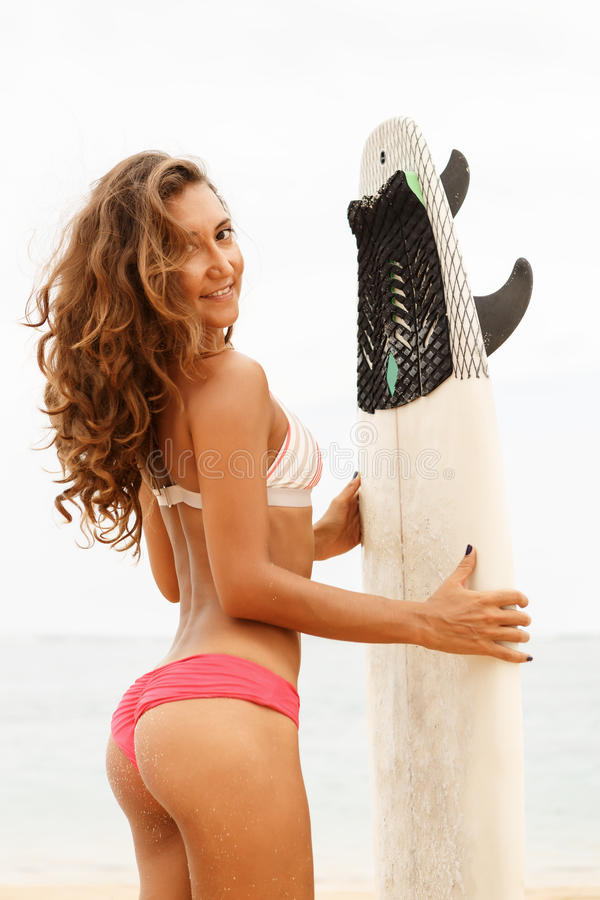 Menina desportiva bonita do surfista na praia imagens de stock royalty free