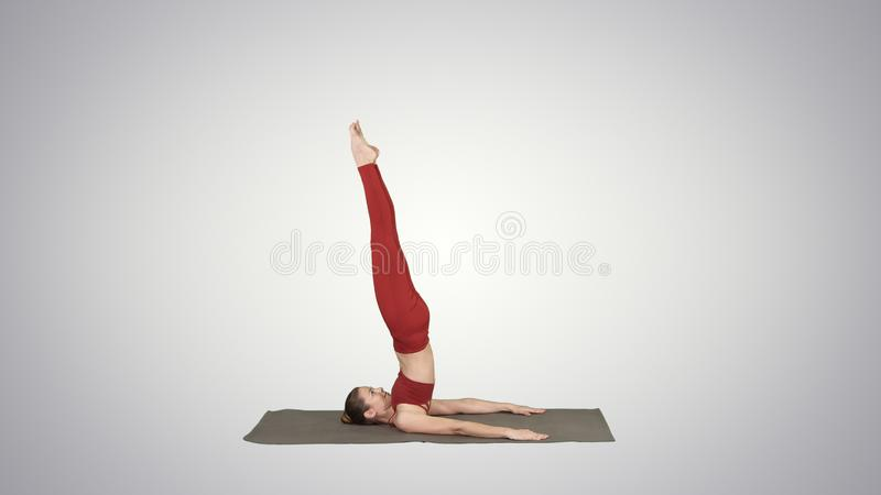 A menina desportiva bonita que faz exercícios da ioga para a força do Abs, apoiou o asana de Shoulderstand, Salamba Sarvangasana  ilustração do vetor