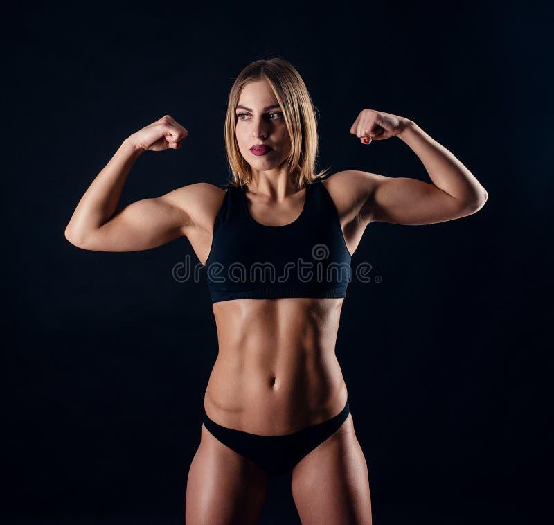 Menina desportiva com os grandes músculos no sportswear preto Mulher atlética nova bronzeada Um corpo fêmea do grande esporte imagem de stock royalty free