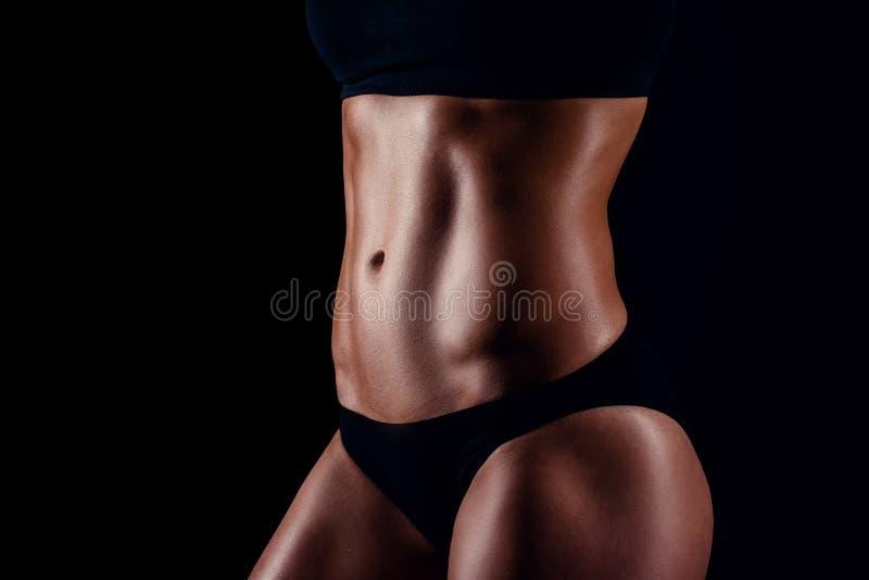 Menina desportiva com os grandes músculos no sportswear preto Mulher atlética nova bronzeada Um corpo fêmea do grande esporte fotos de stock royalty free