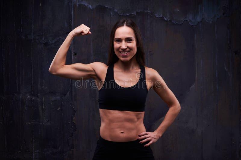 Menina desportiva da aptidão que mostra lhe bíceps bem treinado contra o blac foto de stock royalty free