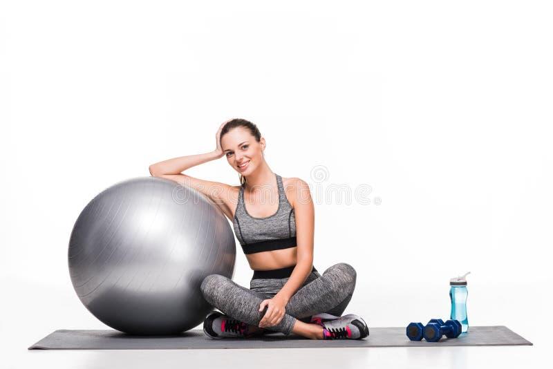 menina desportiva feliz atrativa que senta-se com bola da aptidão e que sorri na câmera fotografia de stock