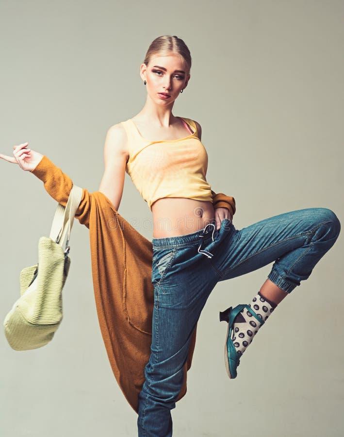 Menina desportiva nas peúgas engraçadas que saltam com o saco verde em suas mãos isoladas no fundo cinzento fotografia de stock