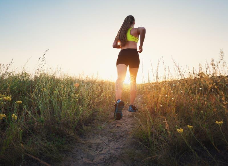 Menina desportiva nova que corre em uma estrada rural no por do sol imagem de stock royalty free
