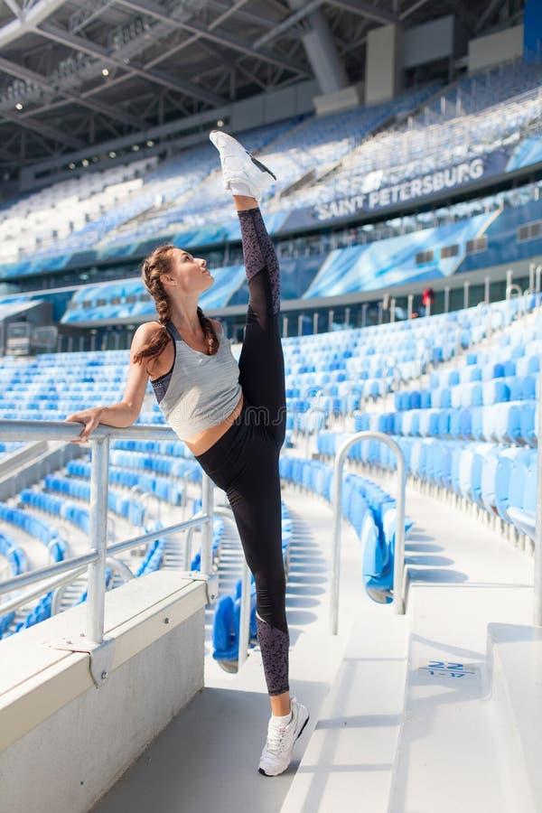 Menina desportiva nova que faz o exercício no estádio Levantou seu pé acima sobre minha cabeça Mulher no sportswear um grande est imagem de stock