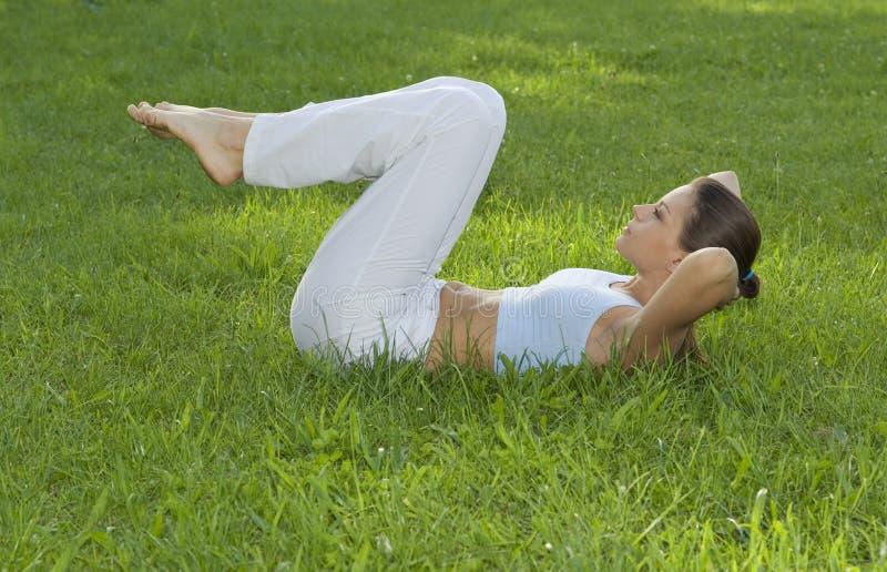 Menina desportiva que exercita no prado de encontro ao céu imagens de stock