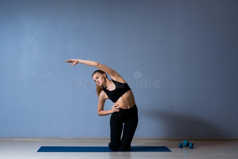 Menina desportiva que faz esticando exercícios foto de stock