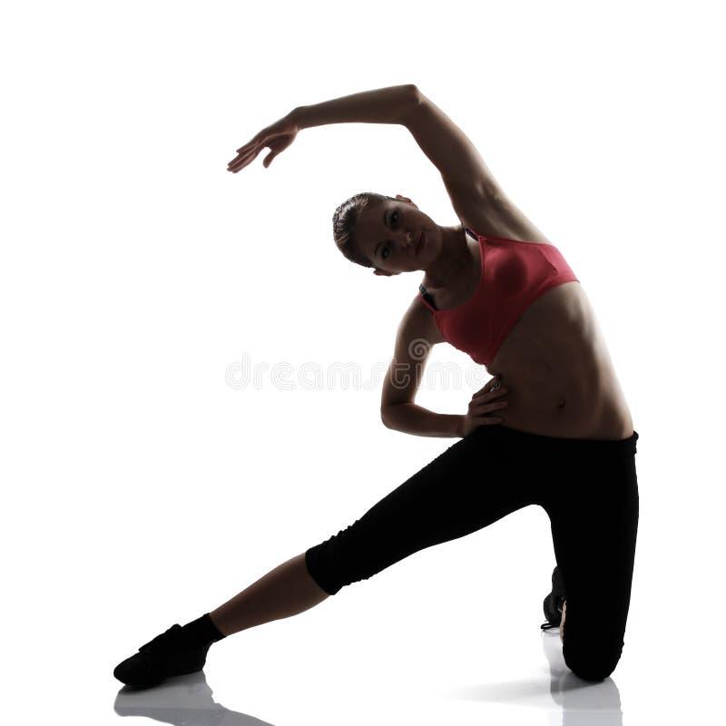 A menina desportiva que faz o Abs exercita, mostra em silhueta o estúdio disparado sobre o whit imagem de stock royalty free