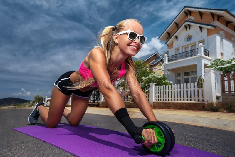 Menina desportiva que faz o exercício com um rolo fotos de stock royalty free