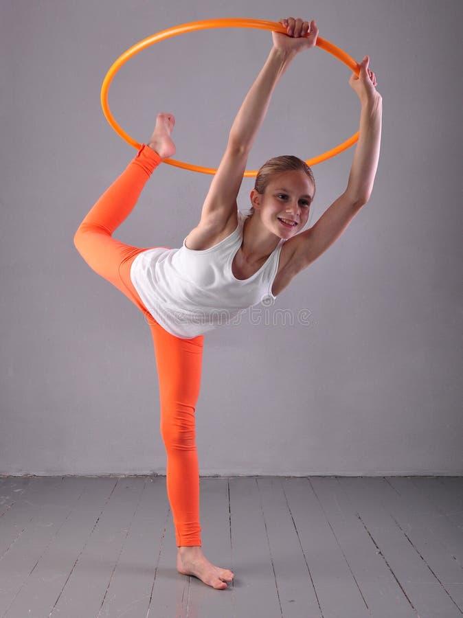 A menina desportivo adolescente está fazendo exercícios com aro t do hula no fundo cinzento Tendo o divertimento que joga o jogo  imagem de stock