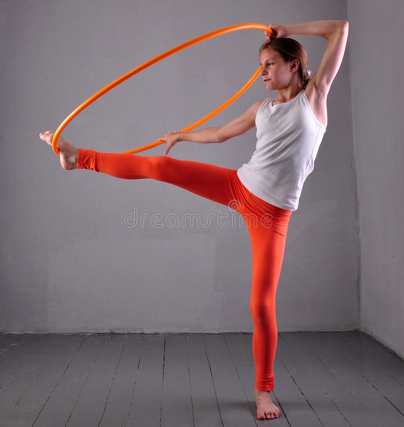 A menina desportivo adolescente está fazendo exercícios com aro t do hula no fundo cinzento Tendo o divertimento que joga o jogo  imagens de stock royalty free
