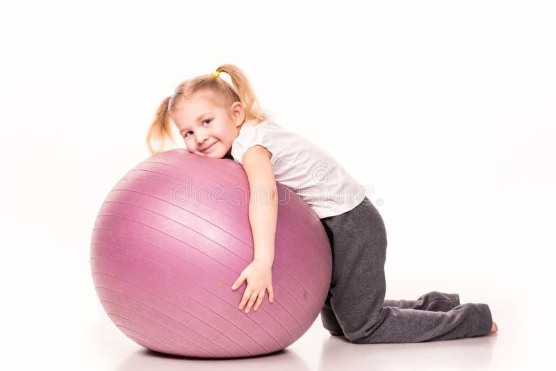 Menina desportivo em uma bola do ajuste isolada sobre o branco fotografia de stock royalty free