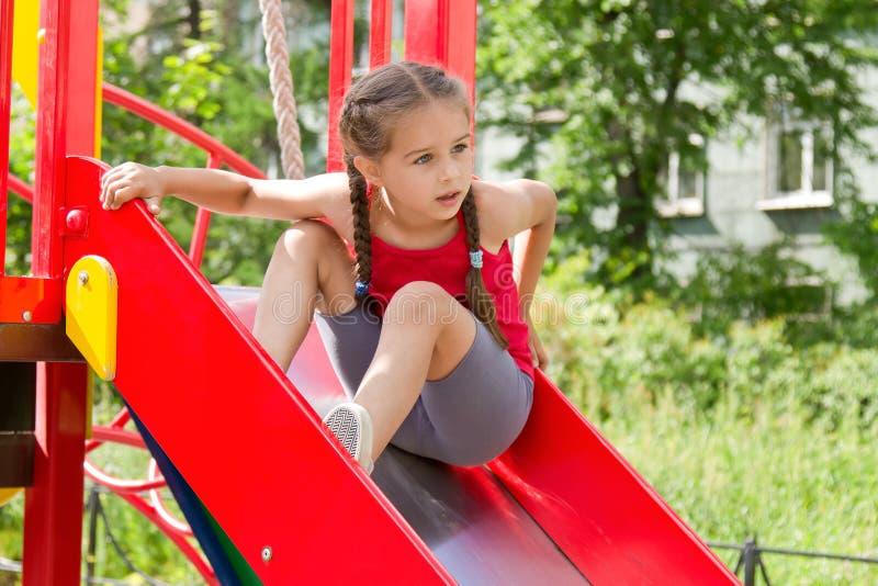 Menina desportivo pequena que joga no campo de jogos, sentando-se na corrediça fotografia de stock