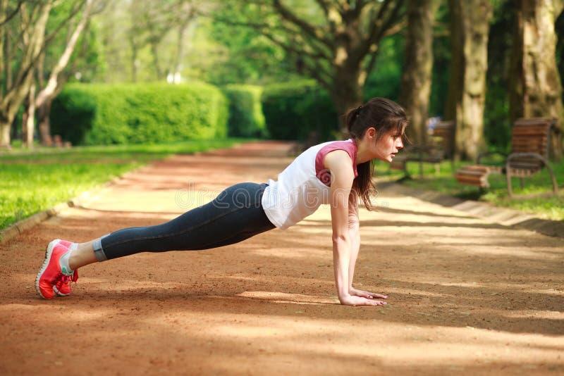 A menina desportivo que dá certo fazer empurra levanta o exercício da imprensa foto de stock