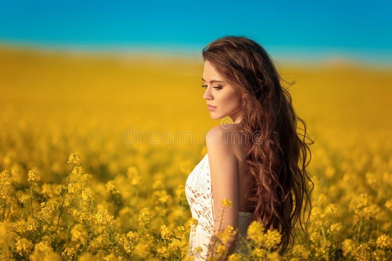 Menina despreocupada bonita com cabelo saudável encaracolado longo sobre o fundo amarelo da paisagem do campo da violação Morena  fotografia de stock royalty free
