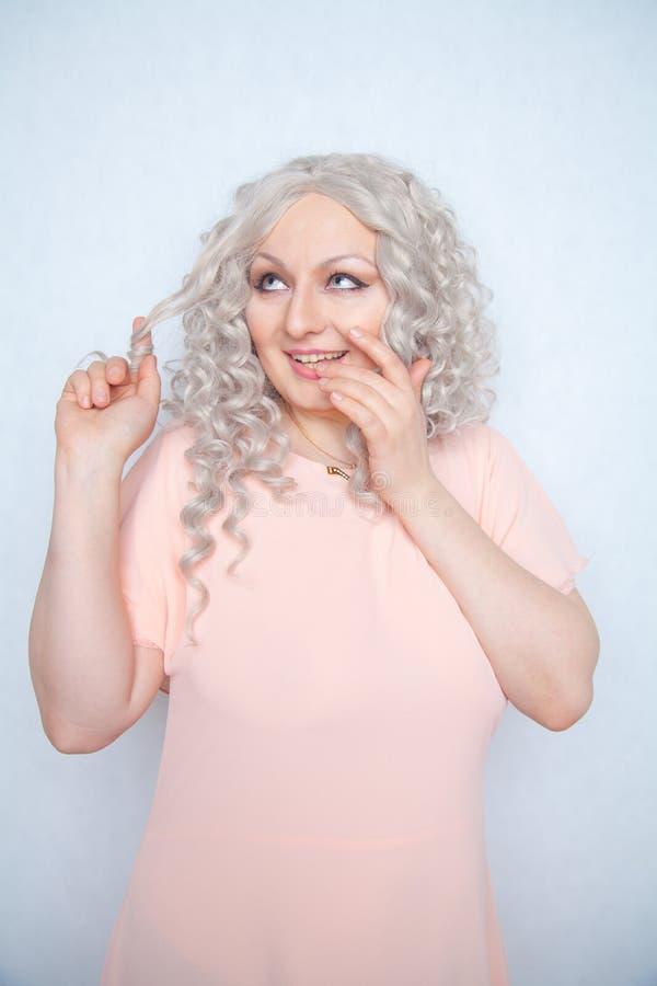 A menina despreocupada em um vestido cor-de-rosa torce seu cabelo encaracolado louro em seu dedo e exulta-o em um fundo monocromá imagens de stock