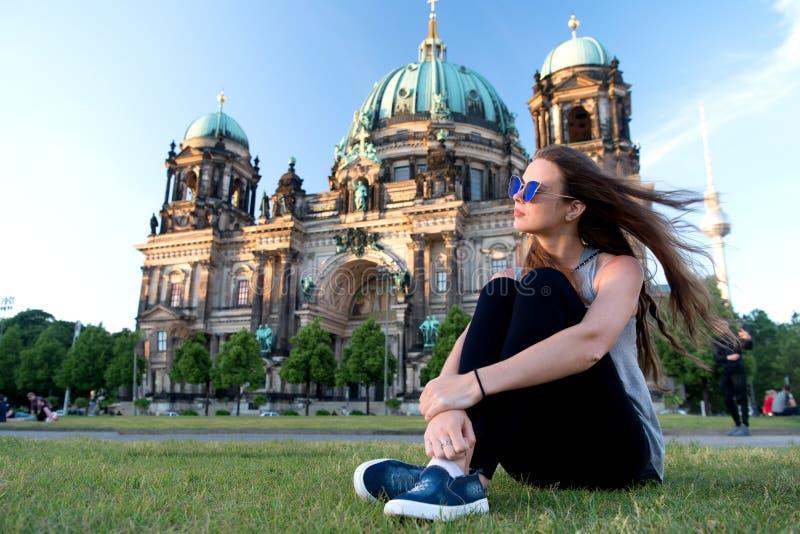 A menina despreocupada relaxa em Alemanha na catedral de Berlim a menina bonita relaxa na grama do verão perto da catedral de Ber foto de stock