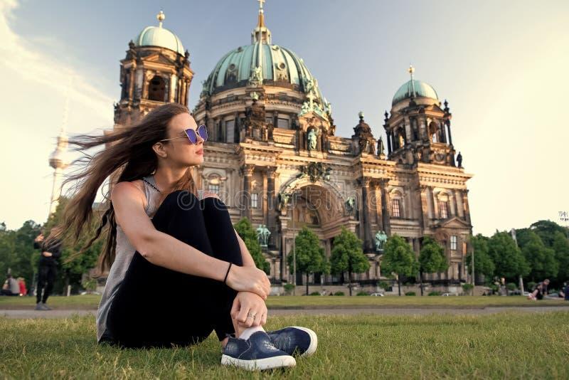 A menina despreocupada relaxa em Alemanha na catedral de Berlim a menina bonita relaxa na grama do ver?o perto da catedral de Ber imagens de stock