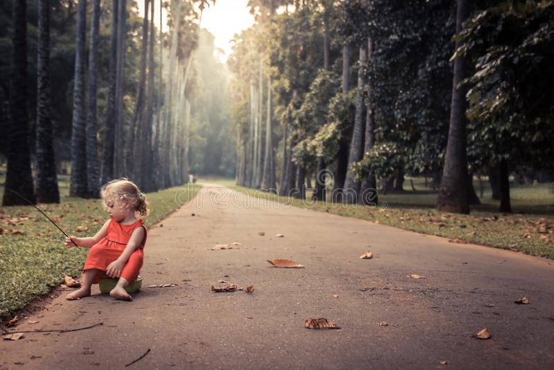 Menina despreocupada só da criança que joga na estrada da solidão sozinha do conceito do parque no estilo de vida despreocupado d fotos de stock royalty free