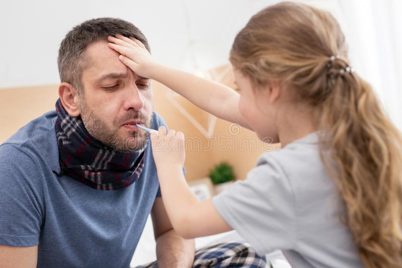Menina determinada que trata seu pai doente fotografia de stock