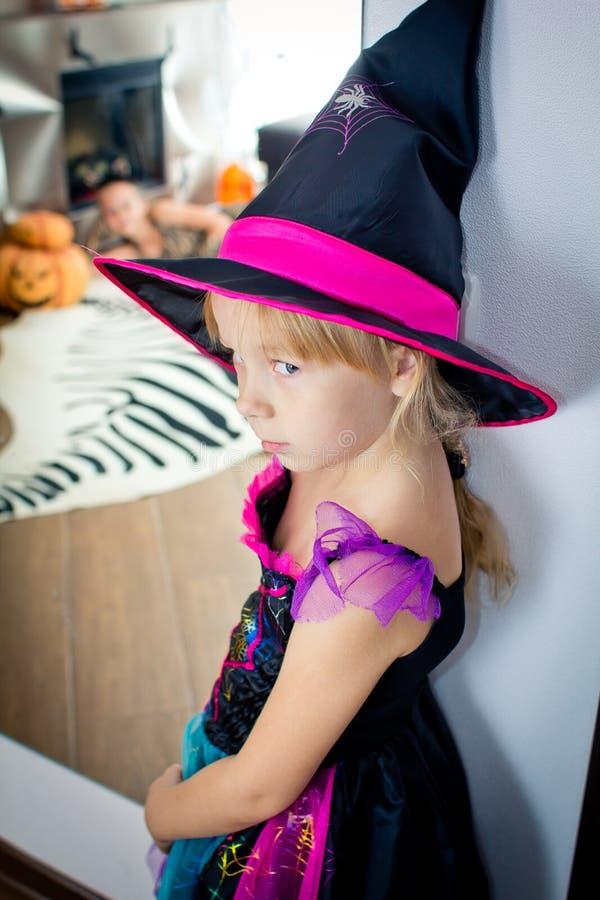 A menina disfarçada como a bruxa está estando perto de um espelho fotografia de stock