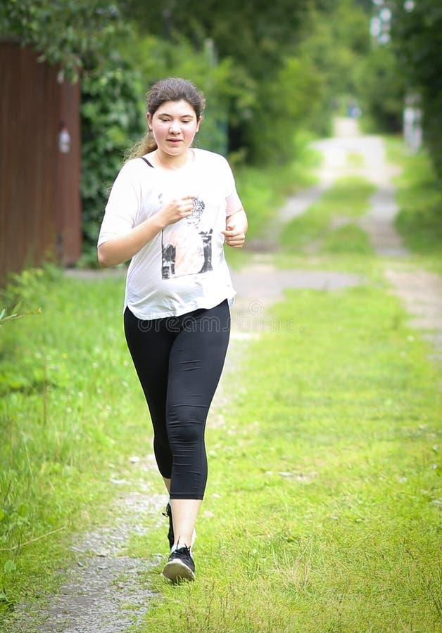 Menina do adolescente com o cabelo escuro longo que movimenta-se na estrada coutry do verão fotos de stock