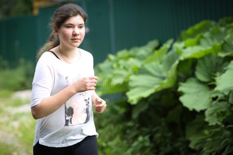 Menina do adolescente com o cabelo escuro longo que movimenta-se na estrada coutry do verão imagem de stock royalty free