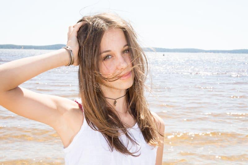 menina do adolescente com o cabelo que funde no vento ao lado do mar fotografia de stock