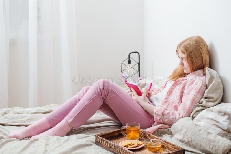 Menina do adolescente com o diário cor-de-rosa na cama imagem de stock