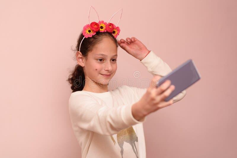 Menina do adolescente com o diadema das flores que tomam o selfie com seu telefone celular no fundo cor-de-rosa fotos de stock royalty free