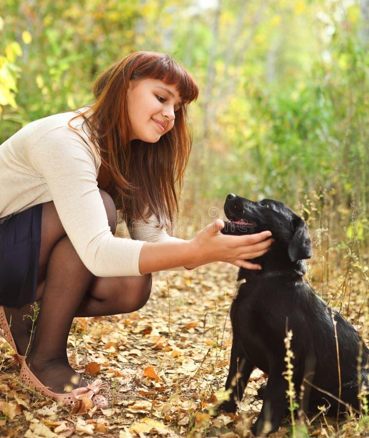 Menina do adolescente com o filhote de cachorro preto do retriever de Labrador foto de stock