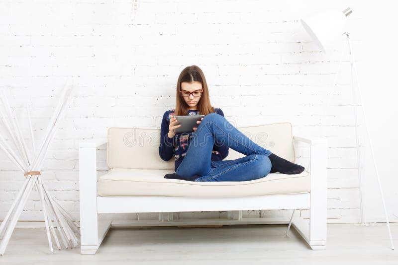 A menina do adolescente com PC da tabuleta relaxa em casa fotografia de stock