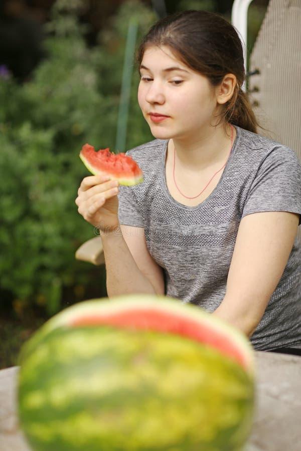 A menina do adolescente come o fim cortado da fatia da melancia acima da foto fotografia de stock royalty free