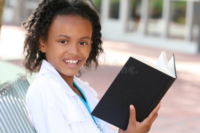 Menina do adolescente do americano africano que lê um livro fotografia de stock