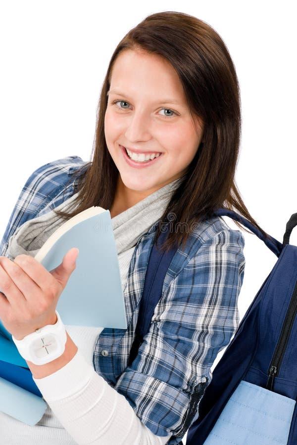 A menina do adolescente do estudante com schoolbag leu livros imagens de stock royalty free