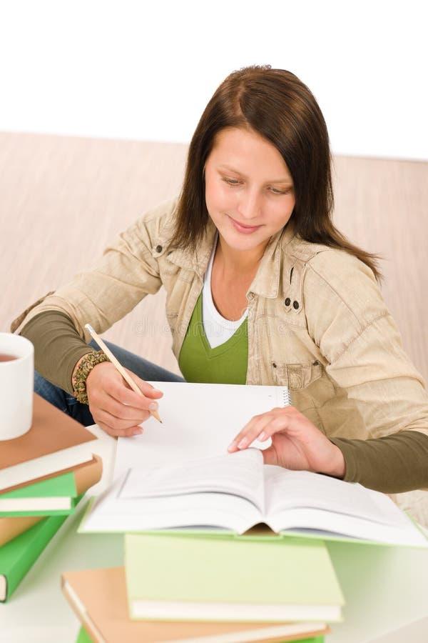 A menina do adolescente do estudante escreve trabalhos de casa com livro fotografia de stock