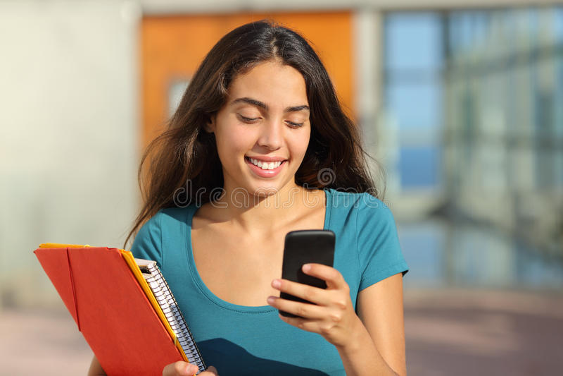 Menina do adolescente do estudante que anda ao olhar seu telefone esperto fotos de stock royalty free