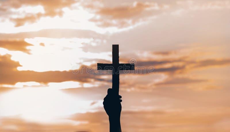 Menina do adolescente guardando a cruz à disposição durante o por do sol bonito M?os dobradas no conceito da ora??o para a f? fotos de stock royalty free