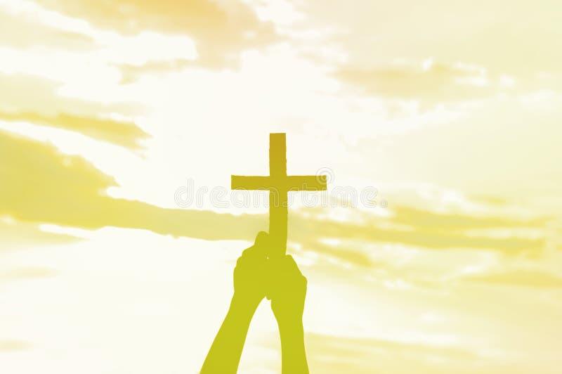 Menina do adolescente guardando a cruz à disposição durante o por do sol bonito M?os dobradas no conceito da ora??o para a f? imagens de stock royalty free