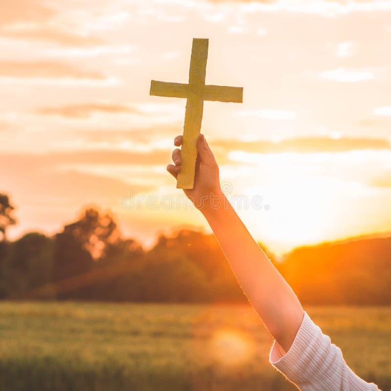 Menina do adolescente guardando a cruz à disposição durante o por do sol bonito M?os dobradas no conceito da ora??o para a f? imagens de stock